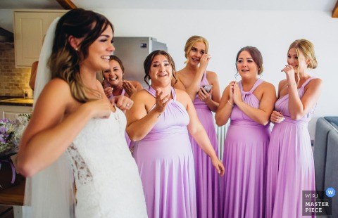 Bridesmaids take a first look at Bride in her dress at Quantock lakes