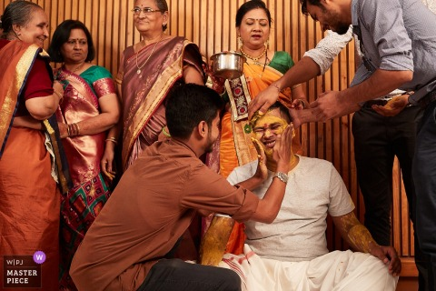 A man puts yellow paste on the groom's face as part of the ceremony in Nadiad, India in this award-winning image by a Florence, Tuscany wedding photographer.