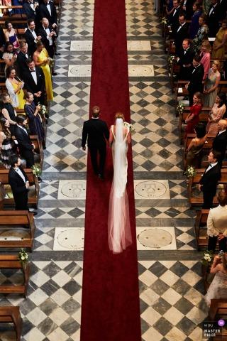 Długa zasłona panny młodej przebiega za nią, gdy wraz z ojcem idą do ołtarza na tym zdjęciu ślubnym uchwyconym przez wielokrotnie nagradzanego fotografa z Florencji.