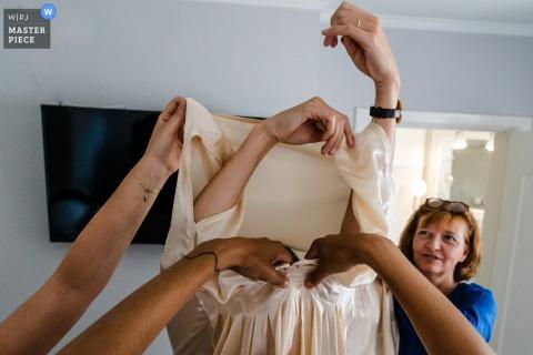 Auf diesem Hochzeitsfoto eines preisgekrönten flämischen Fotografen helfen Frauen der Braut, sich bei Filmfabriek Bierbeek anzuziehen.