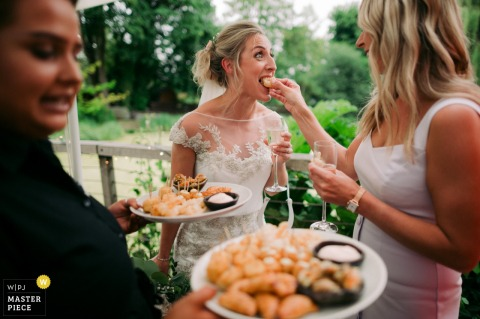 A guest feeds the bride a bite of food during her reception at Tuddenham Mill, UK in this image taken by a West Midlands, England wedding photographer.