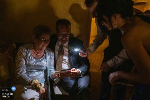 La Venta Inn, Palos Verdes Estates, CA Wedding Photography | The father and grandmother of the bride look at a photo together in the dark as wedding guests light it with a cellphone flash.