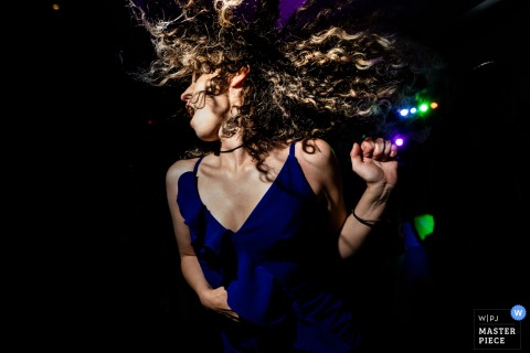 Atlanta wedding reception guest dancing under the dj lights with her hair flying