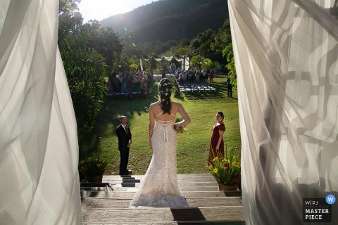 Gli ospiti guardano mentre la sposa scende le scale a Estalagem Alter Real a Pirenópolis in questa foto di matrimonio scattata da un fotografo documentarista di Goias, in Brasile.