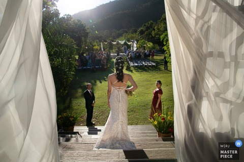 Guests watch as the bride descends the stairs at Estalagem Alter Real in Pirenópolis in this wedding photo captured by a Goias, Brazil documentary photographer.