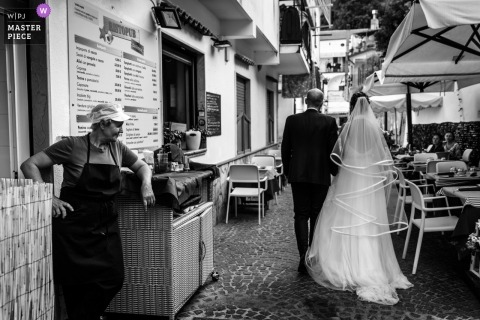 A wedding bridal walk through Erchie as a restaurant vendor looks on.
