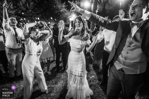 Imagen de la boda en blanco y negro de Taormina capturando a la novia y su invitado bailando en su recepción.