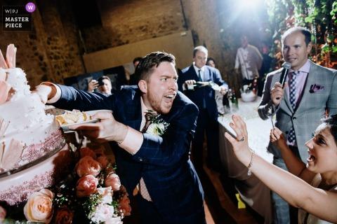 Humorystyczny wizerunek pana młodego na weselu sięgający do ciasta gołymi rękami w El Convento de Blanes