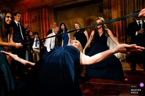 A wedding reception photograph of a woman doing the limbo at Hotel Jerome