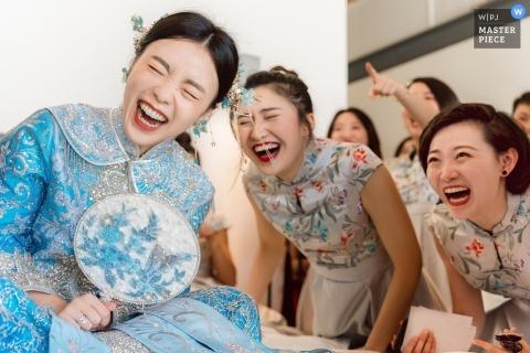 La novia y las damas de honor se reían a carcajadas ante la divertida actuación del novio y los padrinos de boda en la sección de juegos de la puerta, en Sava Beach Villas en Tailandia.