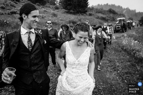 Black and white wedding shot of the newlywed couple walking through rain with guests following at Mountain Top near Bozeman, MT