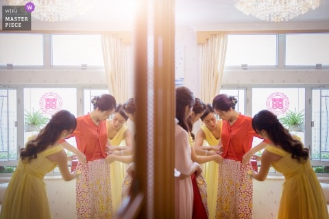 Bride receives assistance in getting ready for her Hong Kong wedding.