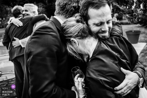Black and white photograph of family hugging at the wedding in Beziers, France