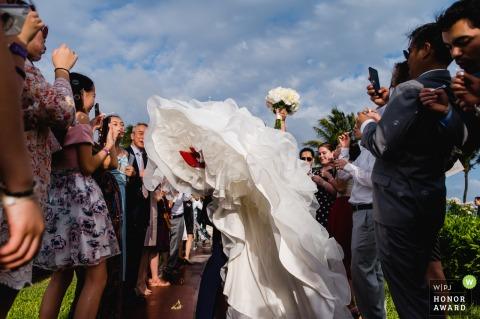 坎昆月亮宫婚礼活动场地照片| 仪式结束时,新郎载着新娘的新郎穿过客人,吹泡泡。