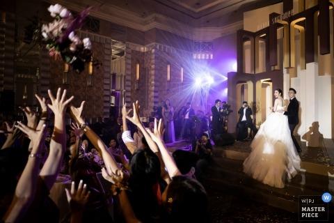 Recepción de boda en InterContinental Bangkok de la novia arrojando su ramo a sus invitados.