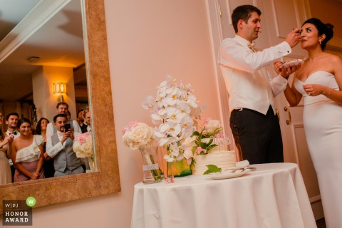 palo alto garden court hotel wedding venue photo - The groom feeds the cake to the bride