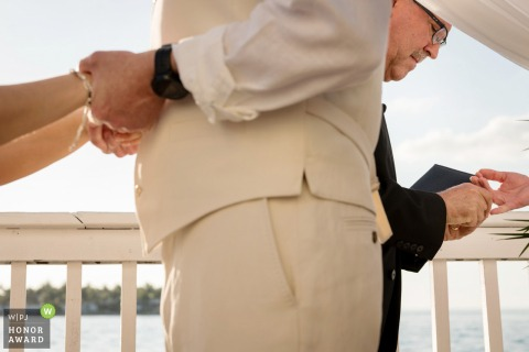 Ocean Key Ring handoff photo during outdoor wedding ceremony in Florida.