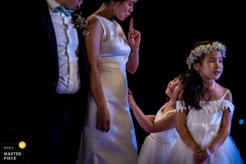 A young girl being told by the bride to be quiet during speeches at a Nha Trang wedding.
