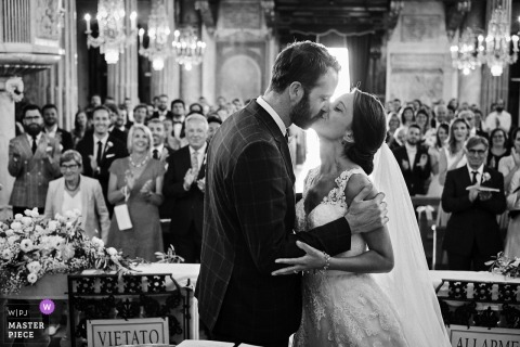 Black and white image of the bride and groom at the altar of Chiesa Di San Giacomo Di Corte during the first kiss.