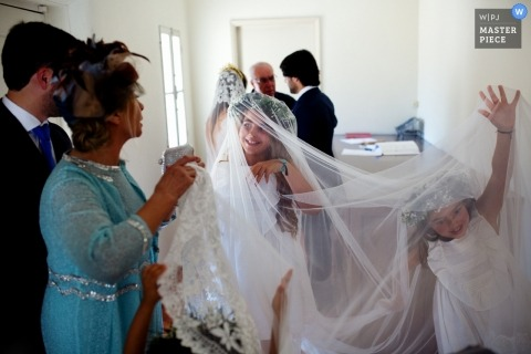 Portugal wedding photo of children playing in the veil of the bride.