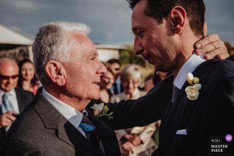 Foto de la boda del padre de la novia conmovida felicitando al novio después de la ceremonia en Vulcano - Therasia Resort