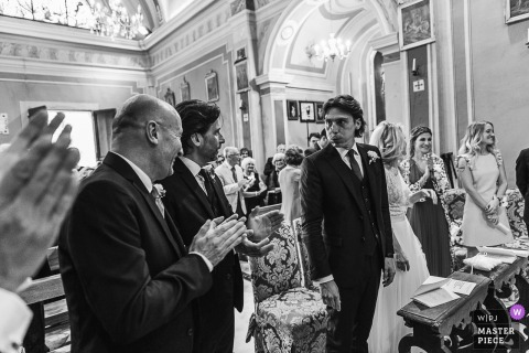 Concerned groom looks to his groomsmen during the ceremony at Chiesa San Michele Arcangelo