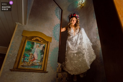 Una novia bajando las escaleras en su casa en Bogotá el día de la boda.