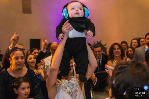 American Jewish University-Brandeis Bardin Campus, Brandeis, California - La novia levanta a un bebé durante una hora, un baile en círculo judío, durante la recepción de su boda.