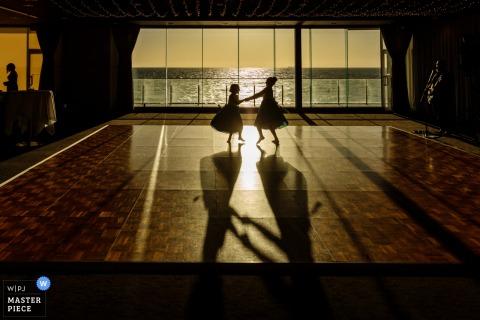 Sandringham Yacht Club - Melbourne Australia Wedding Reportage Photography - Due ragazze di fiori che ballano nella finestra