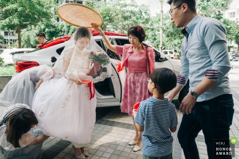 Taichung, Taiwan wedding day photo | The custom of the bride on the road on the local wedding. The sieve above the bride's head symbolizes perfection and guardianship.