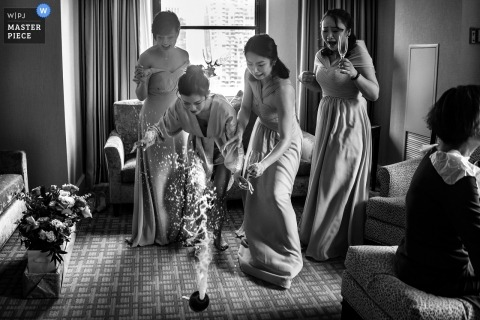 Black and white wedding photography capture of the bride dropping the champagne to the floor in her hotel room at The Arlington Estate, Canada.