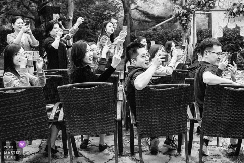 Black and white image of Beijing wedding guests taking photos with their mobile devices.