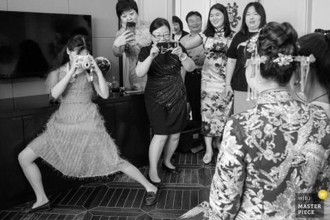 Beijing wedding photograph of bride having her picture taken by her guests in Beijing.
