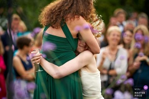 Jardín de padres, Clayton, Reino Unido Fotografía de reportaje de bodas: la novia se acerca para abrazar a su mejor amiga y dama de honor, mientras vacila en su discurso.