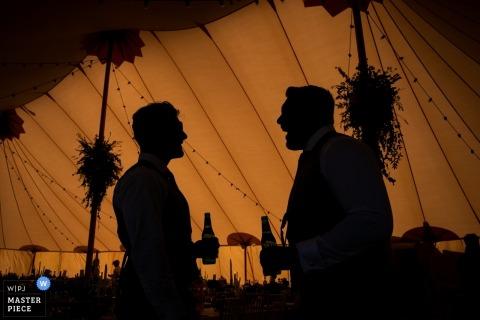 Park Farm, Daventry Tent Fotografía de boda: dos invitados se paran en la carpa para escapar del calor afuera