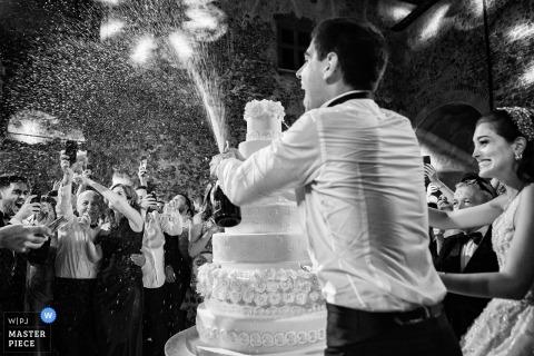 Fotografía del lugar de la boda de Castello Odescalchi: el novio rocía el champán hacia los familiares durante el corte de la torta