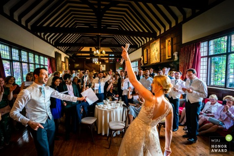 Ramsters Hall wedding venue photo | Bride & Groom in foreground - singalong with guests - colour