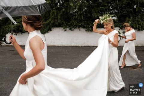 Fotografía de la boda de la Casa Galsson - Novia caminando bajo la lluvia con la dama de honor sosteniendo su vestido largo