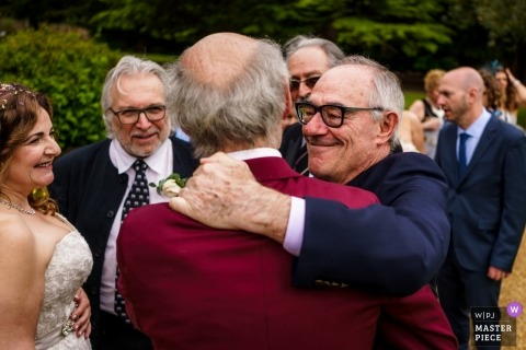 The groom receiving a massive hug from a good friend after the ceremony at the Ettington Park Hotel