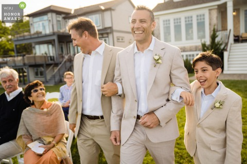 Private Home Outdoor Wedding Ceremony Photo | Groom enters ceremony with his best man and son