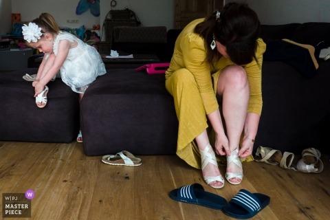 Fotografía del día de la boda de Spiegeltent Glabbeek: prepararse poniéndose los zapatos