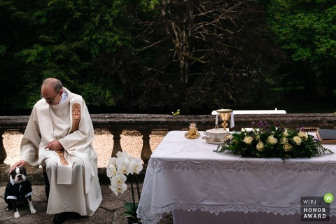 Wedding Photography from a Privately owned castle. Priest pets dog during ceremony