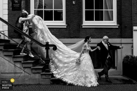 Braut mit Vater auf dem Weg zur Zeremonie in De Krijtberg - Amsterdam - Hochzeitsfotografie