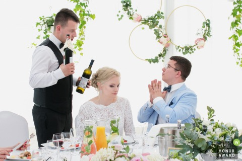 Cracow wedding reception photo | The groom asks for wine.