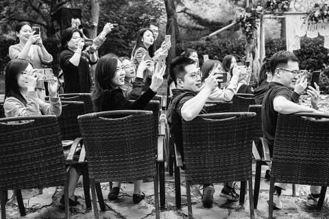 Fotografie die huwelijksgasten toont die foto's van de bruid en bruidegom met hun mobiele apparaten nemen.
