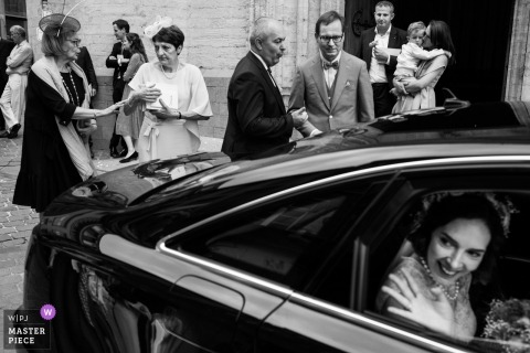 Bride waves to her friends as she leaves in a car, and her guests hang out at the Kasteel van Ruisbroek.
