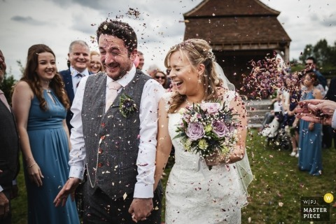 Following a beautiful and emotional wedding ceremony at Redcoats Farmhouse the couple walk down the grass aisle under a storm of confetti, including a new load coming in from the right hand side of the photo. Reactions on their faces are great.