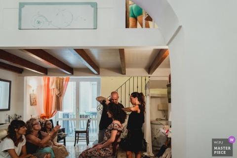 La mariée Napoli prépare sa photographie à la maison avec ses cheveux et son maquillage.