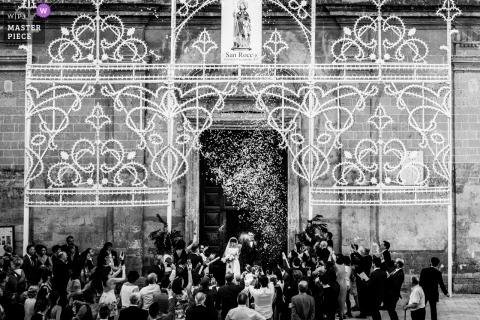Huwelijksfotografie in Puglia van bruid en bruidegom die de ceremonie met gasten vieren.