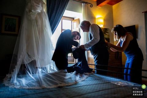 Castrovillari - Tenute Ferrocinto | Fotografie am Hochzeitstag | Die Mutter repariert Papas Weste, während er mit seinem Sohn die Jacke repariert